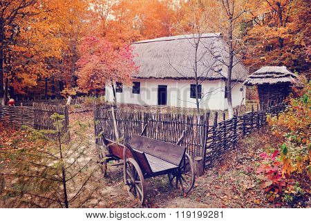 Ukrainian Museum Of Life And Architecture. Ancient Hut With A Straw Roof And Wooden Cart