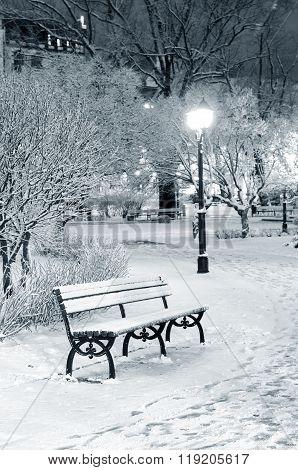 Snow-covered bench in Riga park by night. Cozy winter scene.
