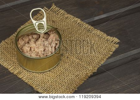 Tuna cans on a dark wooden table. Sales of canned fish. Diet food