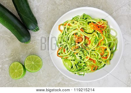 Zucchini noodles with carrots and lime on white marble