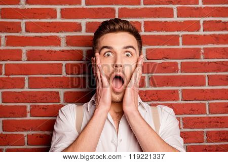 Shocked Young Man Touching His Face On The Background Of Wall