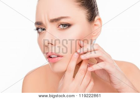 Portrait of young attractive woman touching her face and looking for acne poster
