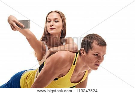man doing push ups and woman selfie