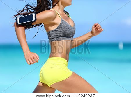 Fitness athlete woman running fast with speed wearing phone armband with touchscreen. Midsection crop showing muscular legs and thighs training glutes during intense cardio workout. poster