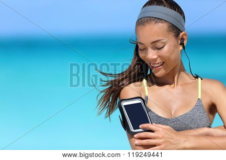 Fit woman using smartphone fitness app on armband. Young Asian female runner touching the display touchscreen on sports arm strap with mobile phone for listening to music or as activity tracker.