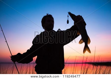 Silhouette of the fisherman with fish and lure