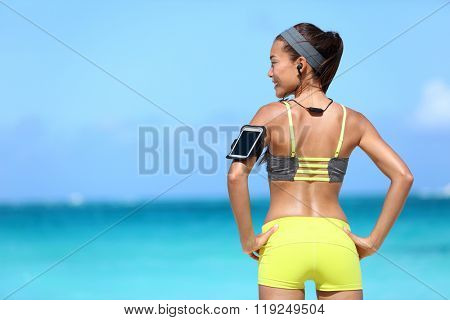Fitness woman listening to music in sportswear with wireless in-ear headphones and sports armband with touchscreen display for smartphone app on summer ocean beach.