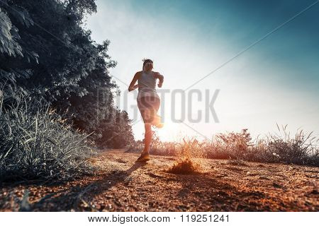 Young woman running on the gravel road at sunset