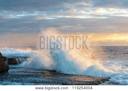 Beautiful ocean with waves on sunrise. Sunrise ocean background with high wave splashing over rocky surface. Nature metaphor of rebellion power strength and energy