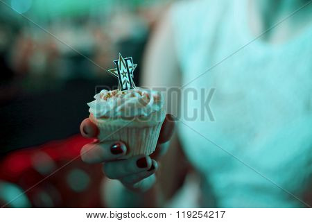 MOSCOW - APR 26, 2015: Female hand holding tasty muffins decorated with cream on the celebration of glossy magazine LF city birthday