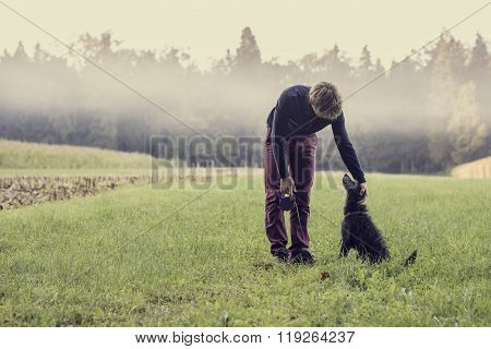 Man Standing In Green Grassland Bending Down To Pat His Black Dog