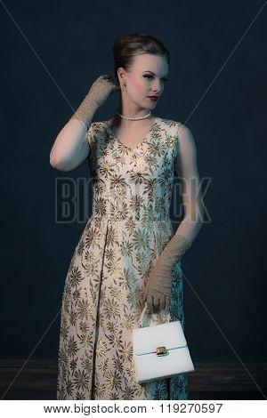 Retro 1950S Posh Fashion Woman In Gold Dress Holding Handbag.