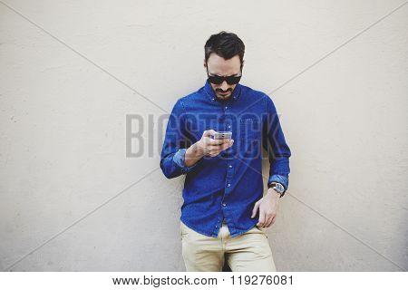 Hipster guy watching video on cell telephone while standing against wall with copy space area