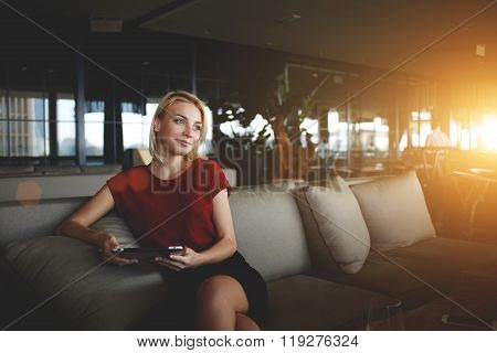 Young female manager waiting for e-mail on digital tablet while sitting in modern office interior