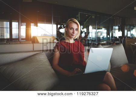 Young woman employer posing during work on net-book in modern comfortable cafe