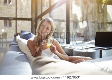 Pretty female student resting after work on net-book while sitting in modern coffee shop
