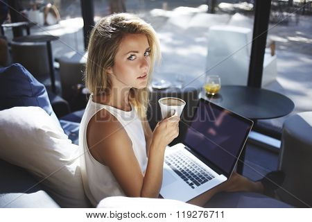 Pretty hipster girl with cup of coffee looking at camera while resting after work on net-book