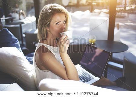 Lovely hipster girl enjoying coffee while waiting downloading a file on net-book