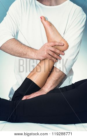 Chiropractic adjustment - Chiropractor working with patient's knee poster