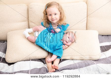 Two Sisters. Older Sister Kid Hugging His Newborn Little Sister. Cute Children Girls Lying On Bed At