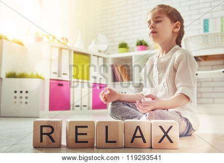 Little child girl playing with blocks and having fun. Blocks have letters. Child arranges cubes and word Relax. Girl is practicing yoga.