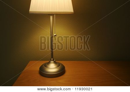 Warm lighting fills this comfortable modern lamp scene with wood desk/table and olive painted wall. Plenty of room for text on the right side.