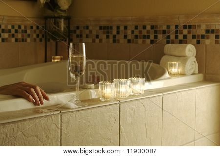 Woman relaxing in a tiled tub. Sparkling wine, candles and towels adorn the scene.