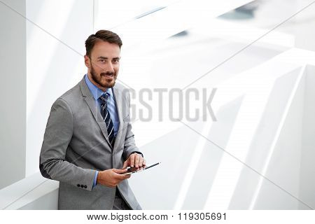 Smiling man economist holding touch pad while standing in modern office interior near copy space
