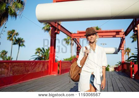 Pretty woman dressed in trendy clothes with backpack on shoulders posing during recreation time
