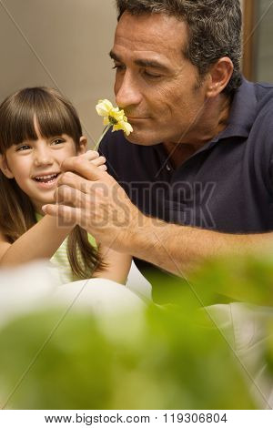 Girl and grandfather smelling flower