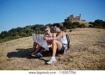 Young man and woman travelers exploring map to continue hiking tour in the countryside in sunny day