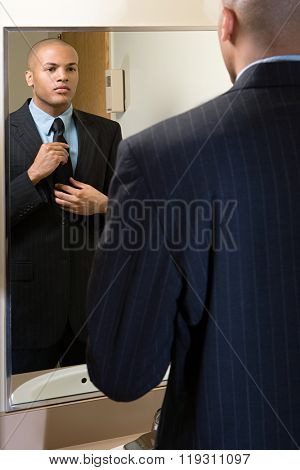 Man adjusting his tie in mirror