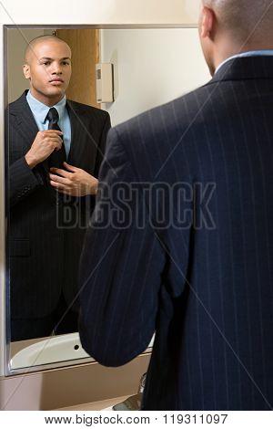 Man adjusting his tie in mirror