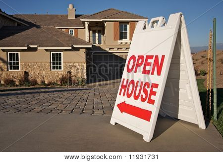 Open House Sign in Front of A Brand New Home. Room for your own message at the top of the sign.