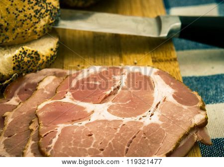Closeup of a carved joint of gammon ham with a carving knife on a wooden board.