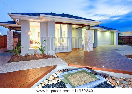 Modern Mansion With Wooden Floor And Concrete Yard And Stone Decorations At Night