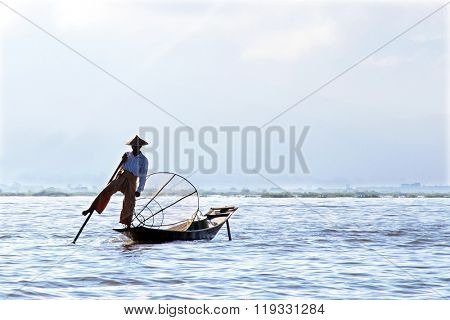 INLE LAKE, MYANMAR - November 15, 2015: Intha people possess the leg-rowing style and the unique coop-like fishing equipment