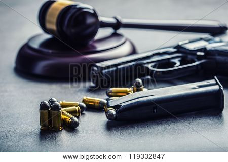 Judge's hammer gavel. Justice and gun. Justice and the judiciary in the unlawful use of of weapons.