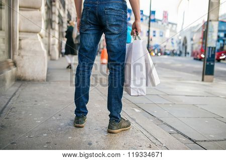 Unrecognizable man with shopping bags in the street, back view