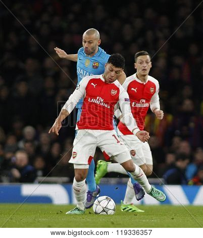 LONDON, ENGLAND - FEBRUARY 23: Javier Mascherano of Barcelona and Alex Oxlade-Chamberlain of Arsenal compete for the ball during the Champions League match between Arsenal and Barcelona