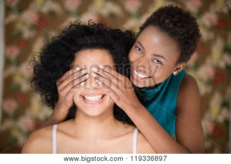 Woman covering friends eyes