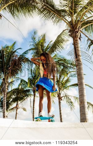 Beautiful Teenage Black Girl In Bright Outfit Rides At Tropical Skatepark.