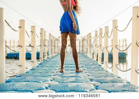 Beautiful Teenage Black Girl In Blue Skirt On Plastic Pier.