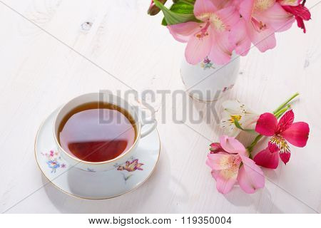 Retro still life with cup of tea and flowers (Alstroemeria) with copy space.
