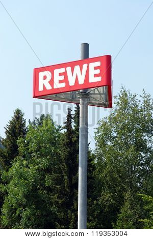 PEITING GERMANY - AUGUST 11 2015: The logo of the REWE supermarket part of the REWE Group - a German retail and tourism group operating in 14 European countries.