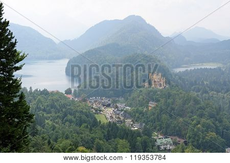 View of Hohenschwangau Castle in a summer foggy day near the lake Alpsee in Bavaria Germany.
