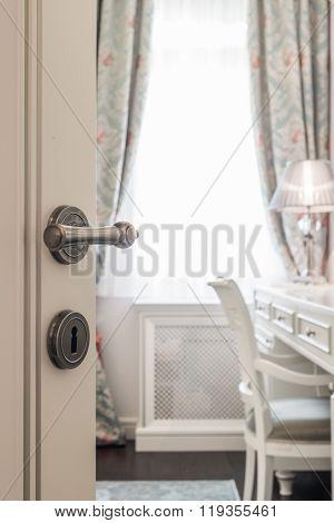 Knob on white wooden door in home interior