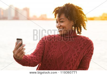 Happy young african woman taking selfie at a river side. Portrait of happy woman taking a photo with modern smartphone. Casual joyful african girl smiling and taking a selfie at sunset.
