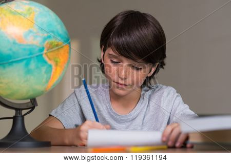 Closeup of little boy doing homework beside globe of earth. Portrait of concentrated boy studying geography. Cute boy doing his homework at desk.