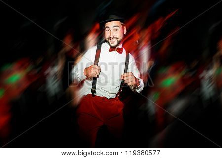 The groom dancing on dance floor, moving in motion. Cheerful man wearing hat and bow tie with suspen